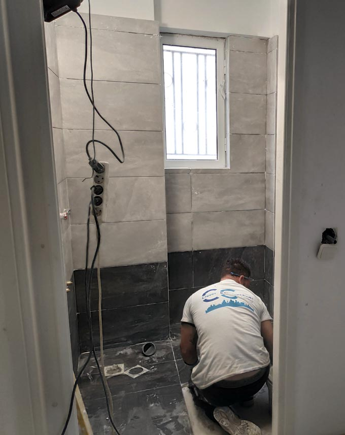 A mason laying porcelain tiles in a bathroom.