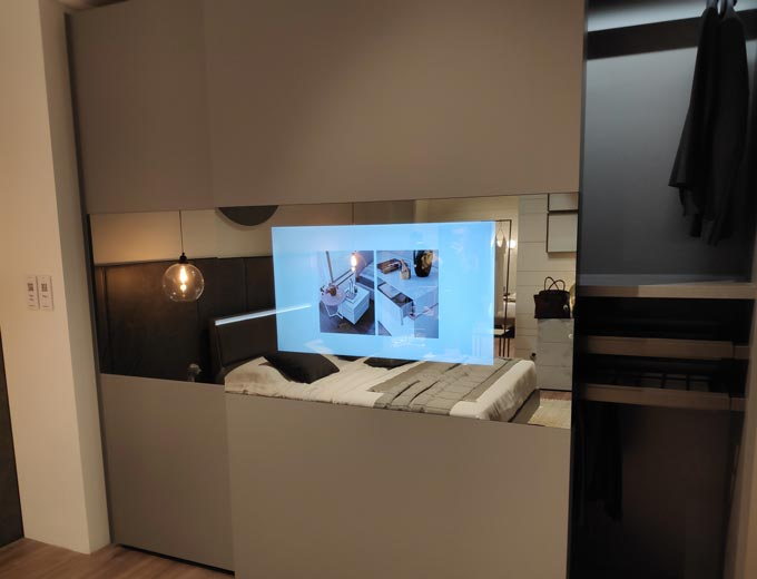 View of a closet's sliding door with a TV monitor embedded within the mirror glass paneling of the door as seen from Maronese ACF at iSaloni 2019 in Milan.