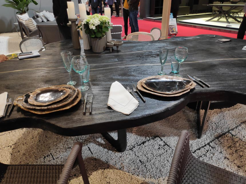 Detail of a dining setting with a dark stained vintage looking dining table from Mary& booth at iSaloni Milan.