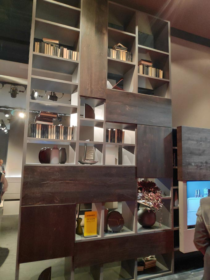 A tall bookcase with dark stained wood panels from Fimar at iSaloni2019 in Milan.