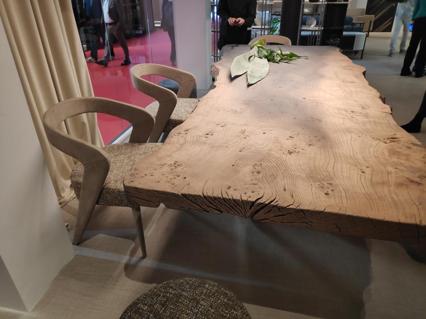 A dining table and curvy dining armchairs with a solid wood frame looking very textured and organic.