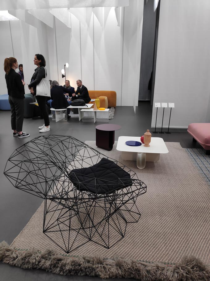 A black truss frame armchair on top of a neutral area rug with a coffee table in the background from the booth of LaCividina at iSaloni in Milan.