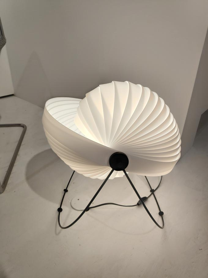 A white floor lamp that looks a bit like a shell from the stand of Objekto at iSaloni 2019 in Milan.