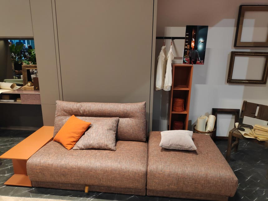 A modular sofa that turns into a bed in front of a closet by Tumidei at iSaloni 2019 in Milan.