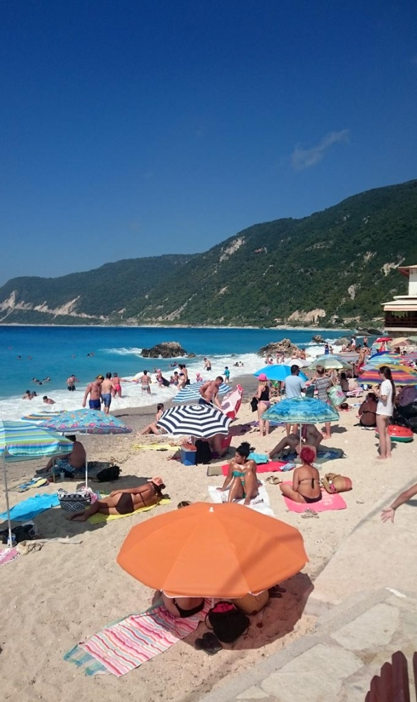 View of the the packed by people Agios Nikitas beach in Lefkada.