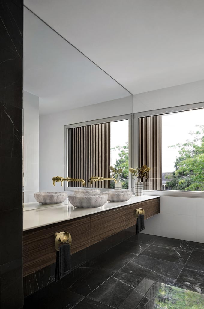 A Contemporary Bathroom with a large bathroom mirror, two wash vessels and black marble flooring.