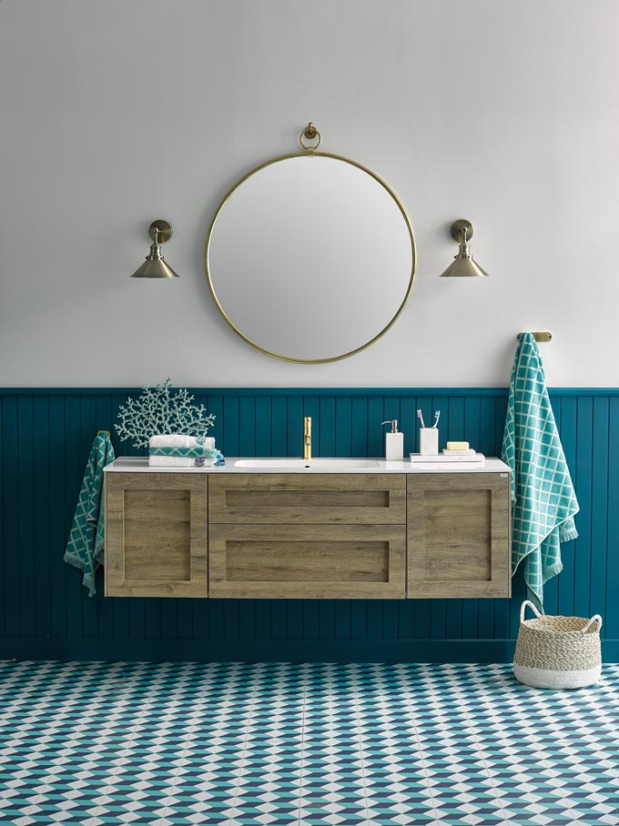 A contemporary bathroom where teal reigns in the wainscotting and flooring. A brassy round mirror is paired nicely with two brassy sconces on each side of it. I like the wall mounted wooden tone vanity furniture that makes everything feel more airy. Image by El Corte Inglés Decoración.