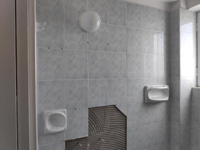 Partial view of a bathroom with old wall tiling before the renovation.