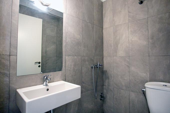 View of a contemporary minimal bathroom with grey wall tiling from a renovation project designed by Velvet Karatzas.