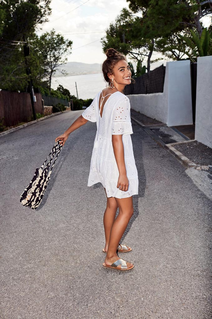 A short white dress with lace details paired with silver flat sandals. Image by Accessorize.