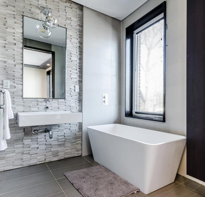 A contemporary bathroom with a textured accent wall behind the wall mounted washbasin and large bathroom mirror.