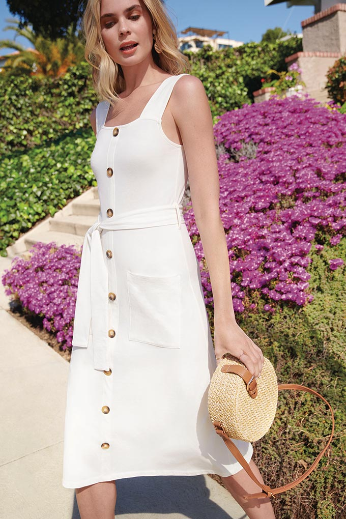 A wide strap button down white dress paired with a straw bag. Image by Dorothy Perkins.