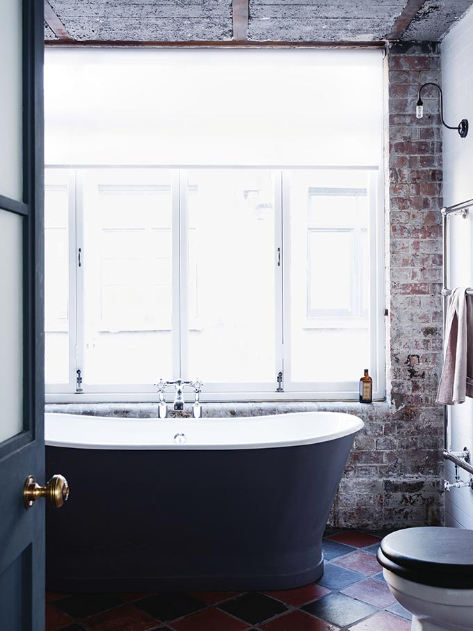 A free standing black tub by a large window with exposed brick walls is as industrial as I'll ever get. I love the simple design of the wall light. Image by Fritz Fryer.