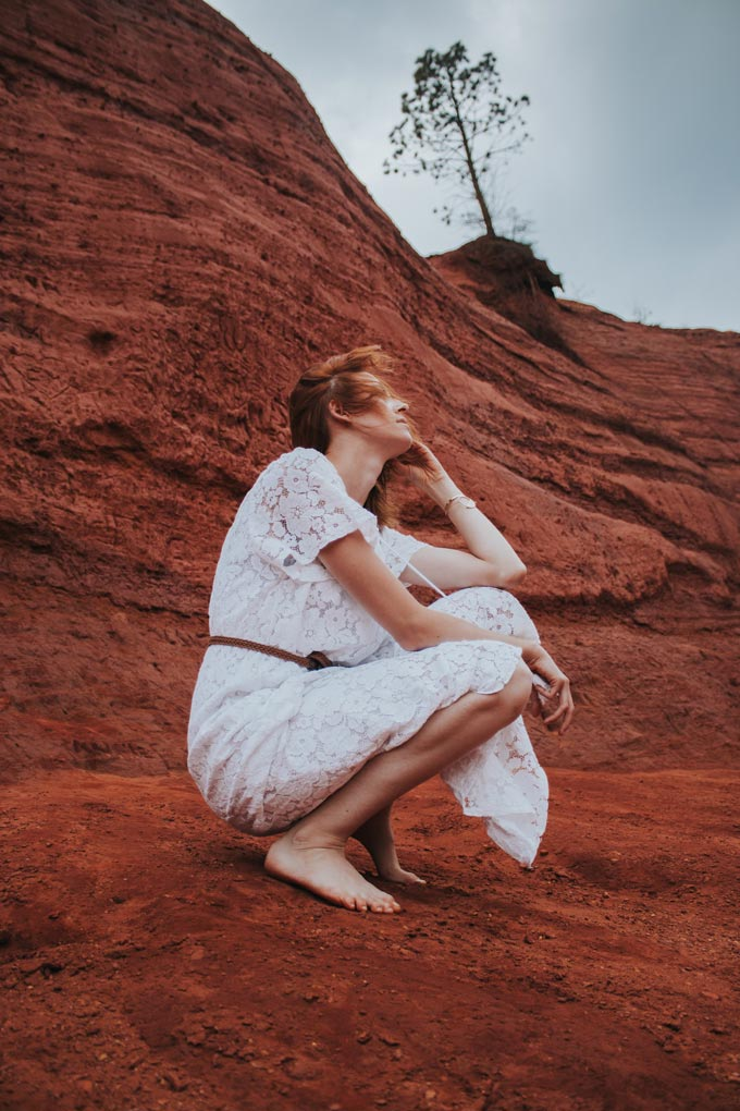 A barefoot red haired woman wearing a summer dress sitting on a red brown rocky mountain side.
