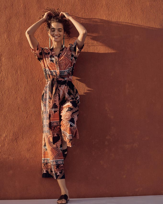 A geometric print jumpsuit in rusty hues and inky stains looks so edgy and refined. Image by Next.
