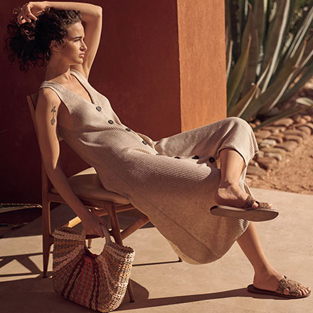 "A beige ribbed jumpsuit with an organic vibe to it paired with a straw bag feels like it's shouting out ""Mediterranean Summer"". Image by Next."