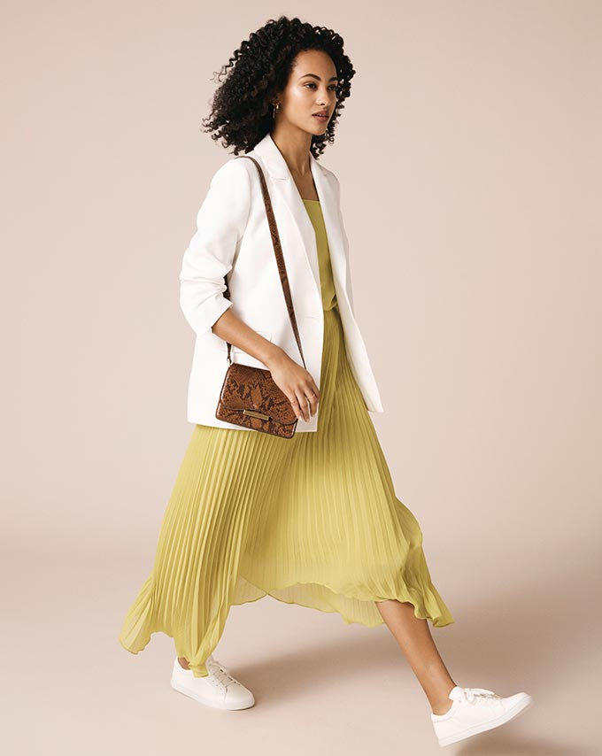 I would love to wear an outfit like this: a white blazer over a pale yellow pleated maxi dress and white sneakers. Image by Oasis.