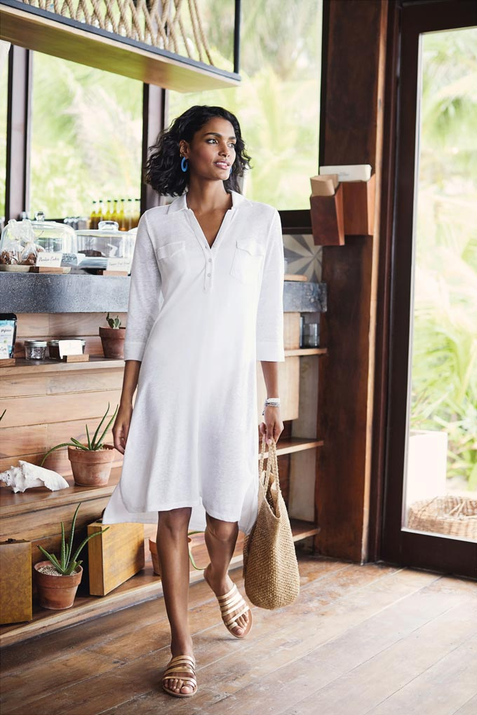 A white knee high dress with a very casual vibe paired with a large straw tote bag. Image by Pure Collection.