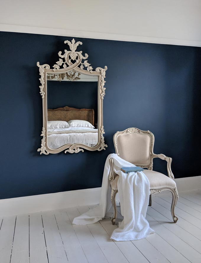 A rectangular mirror with heavy ornamentation against a dark blue wall, next to an off white armchair. Image by The French Bedroom Co.