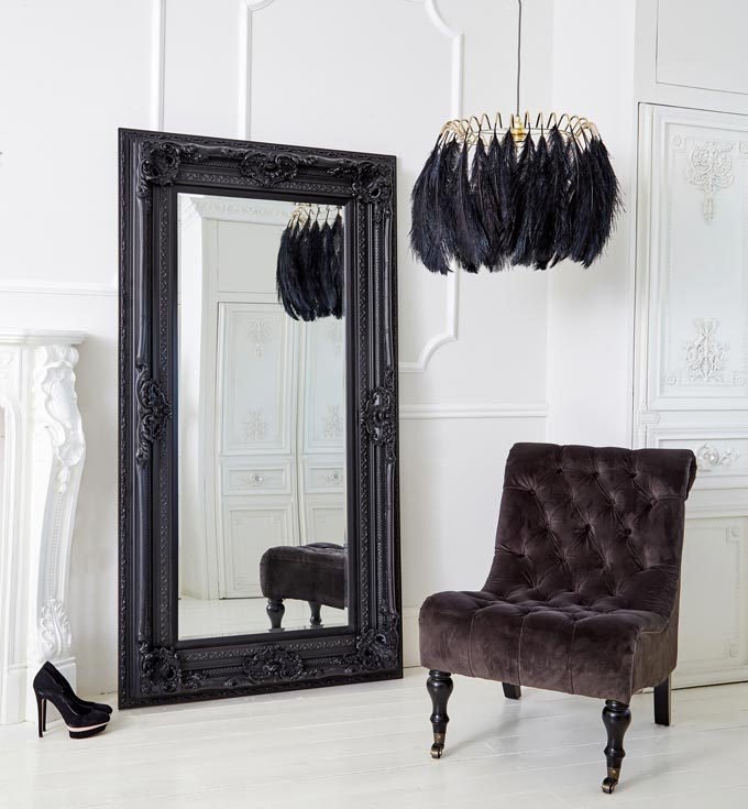 A double black framed French style oversize mirror against a white paneled wall along with a statement pendant light made with black feathers and a black velvet armless chair. Image by The French Bedroom Co.