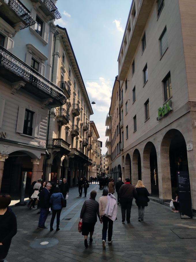 People walking along a pedestrian zone in the old town of Lugano.