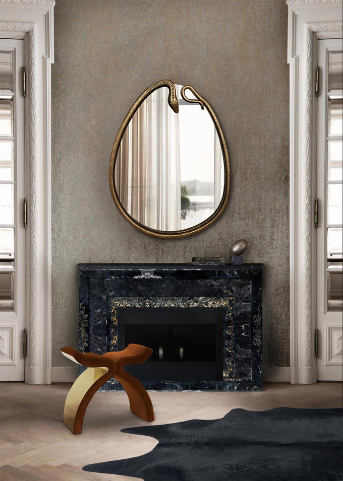 An egg shaped mirror over a black fireplace looking amazing. Image by KOKET.