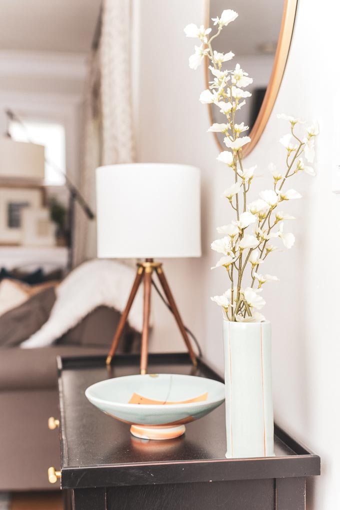Side view of a vignette with white decor over a wooden sideboard against an off white wall.