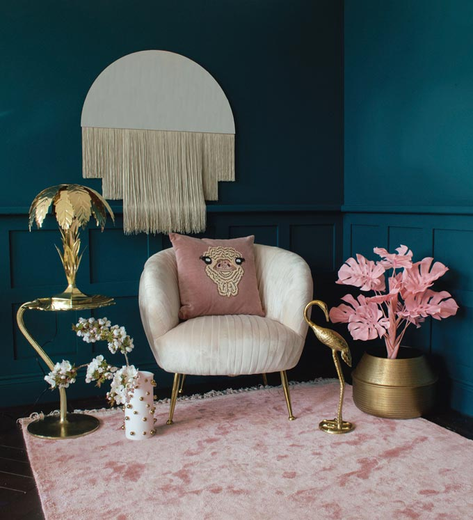 These teal hue wall colors are the perfect background for a curvy off white armchair sitting atop a blush pink area rug and with a half circle mirror decorated with a hanging long fringe. Image by Audenza.