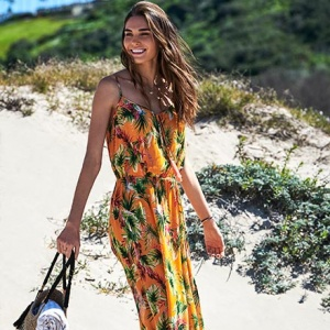 An orange maxi summer dress with a flower print is a great thing to wear when going to the beach along with that straw bag. Love it! Image by Dorothy Perkins.