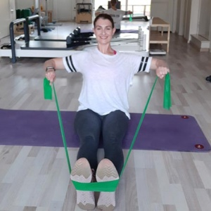 Ifiyenia doing a rowing exercise with a resistance band in a workout that targets the upper body.