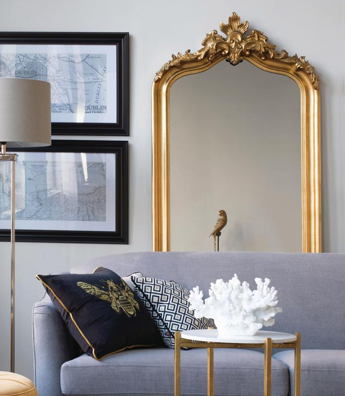 A large mirror standing behind a grey sofa next to two black frames. The setting is contemporary yet with lots of interesting juxtapositions. Image by Harvey Norman.