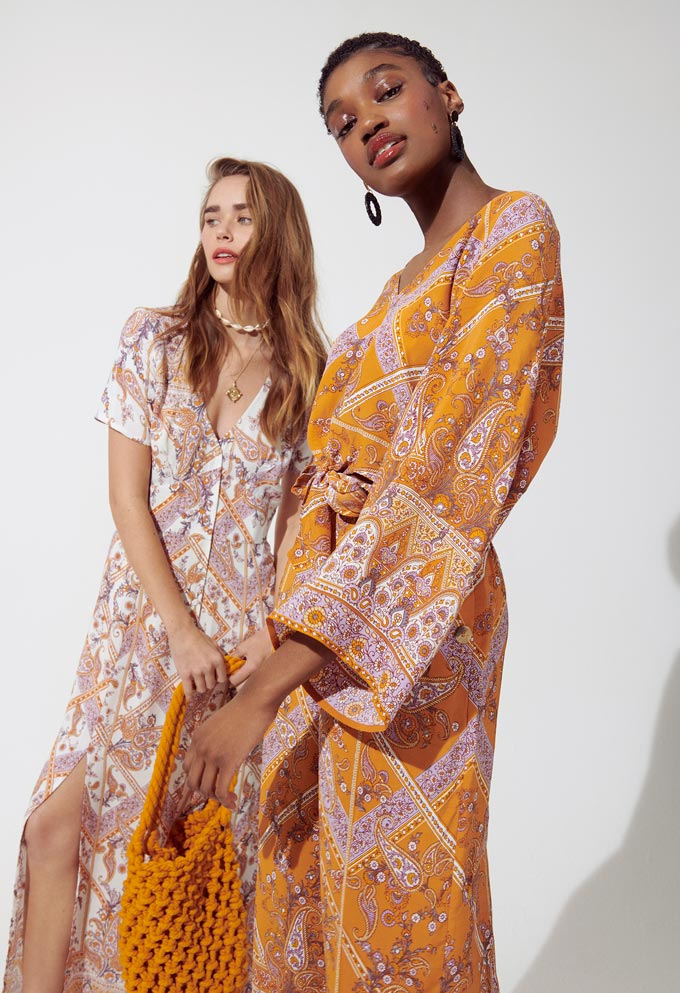 Two women in two orange hue print pattern summer dresses that have a bit of a boho flair to them. Image by Miss Selfridge.