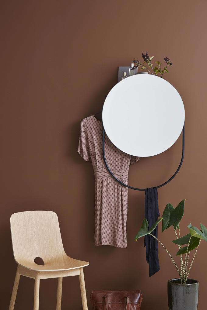 A round mirror that double serves as a hanger as well against a rusty hue wall. Image by Nest.