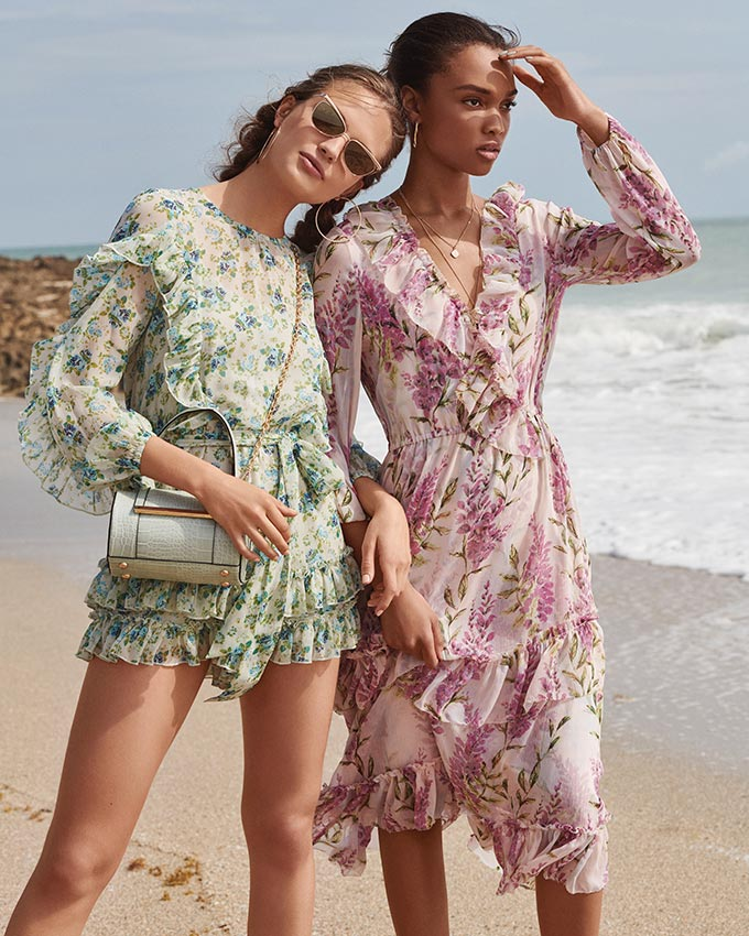 Two women at the beach in summer dresses with a romantic flair to them. The pinkish one with the flower pattern is knee high while the greenish flower print one is very short. Image by River Island.