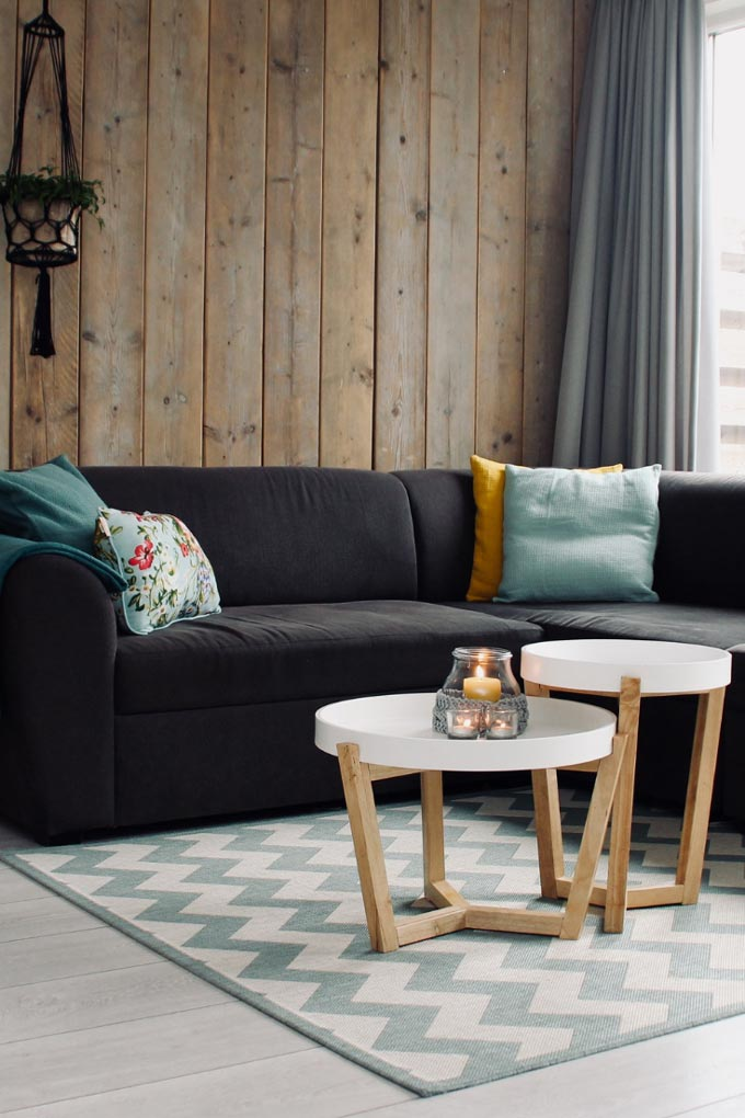 A black sofa in front of an wooden accent wall, sitting on top of an area rug with a chevron pattern.