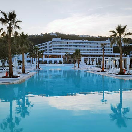 View of the main pool and central building of Grecotel Lux Me Rhodos after sunset hours.