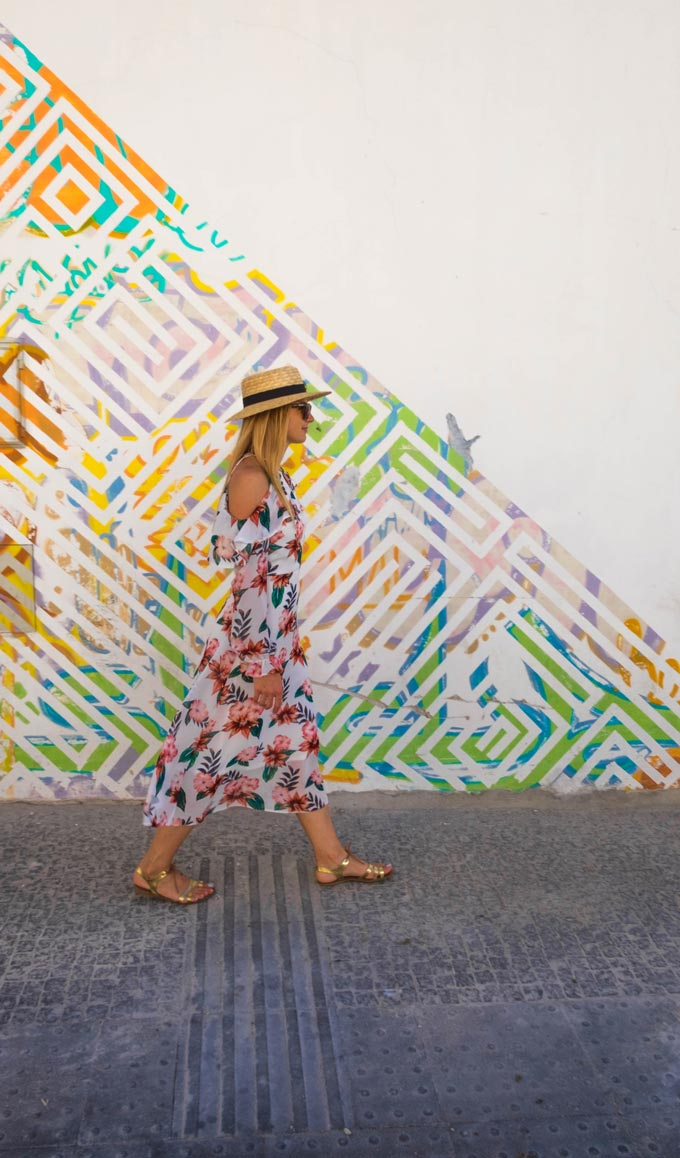 A woman wearing a flower print dress is walking by a wall with a colorful pattern to it.