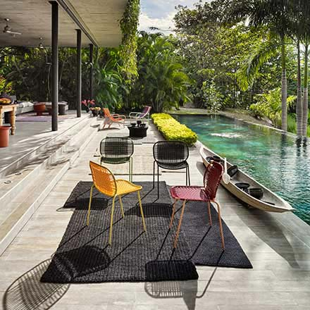 Cielo and circo chairs by an infinity pool somewhere that looks very exotic and tropical.