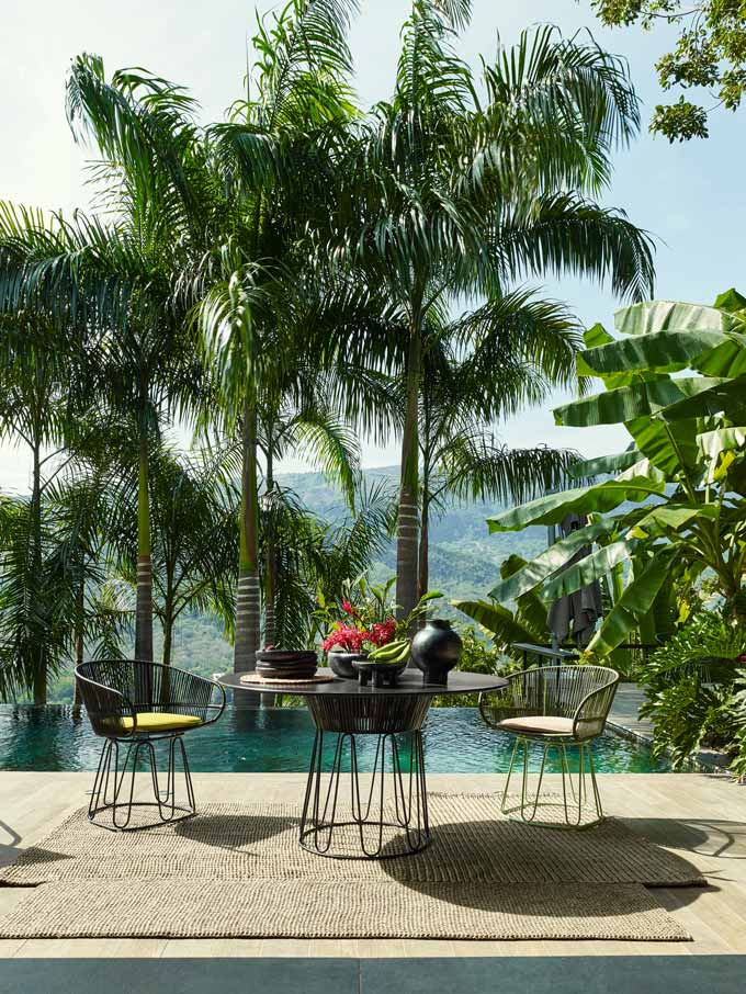 An exotic ames outdoor dining set with an infinity pool and tall palm trees.