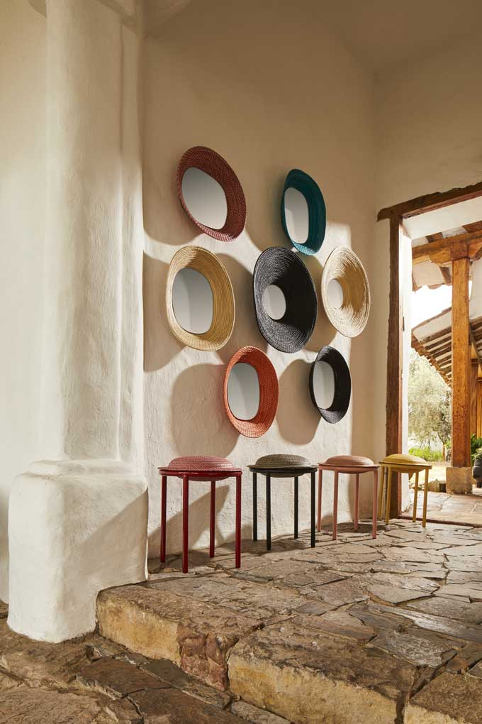 A gallery wall from killa mirrors making a statement and four cana stools underneath them at an entryway.