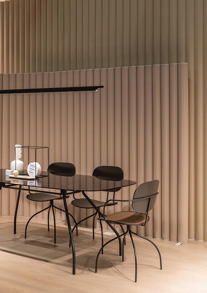 A minimal contemporary dining space with a muted terracotta accent wall made of tubular vertical forms in alignment.