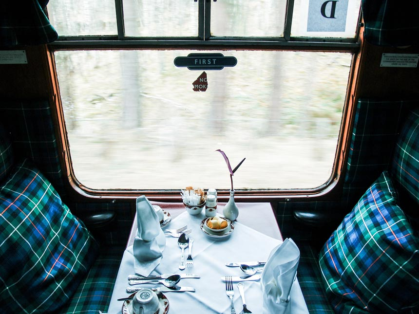The inside of an old first class train car with plaid patterns on the seating benches and pillows.