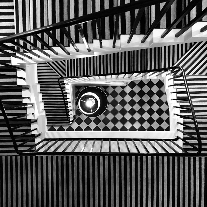 A striking stairwell seen from above because of the different striped patterns.