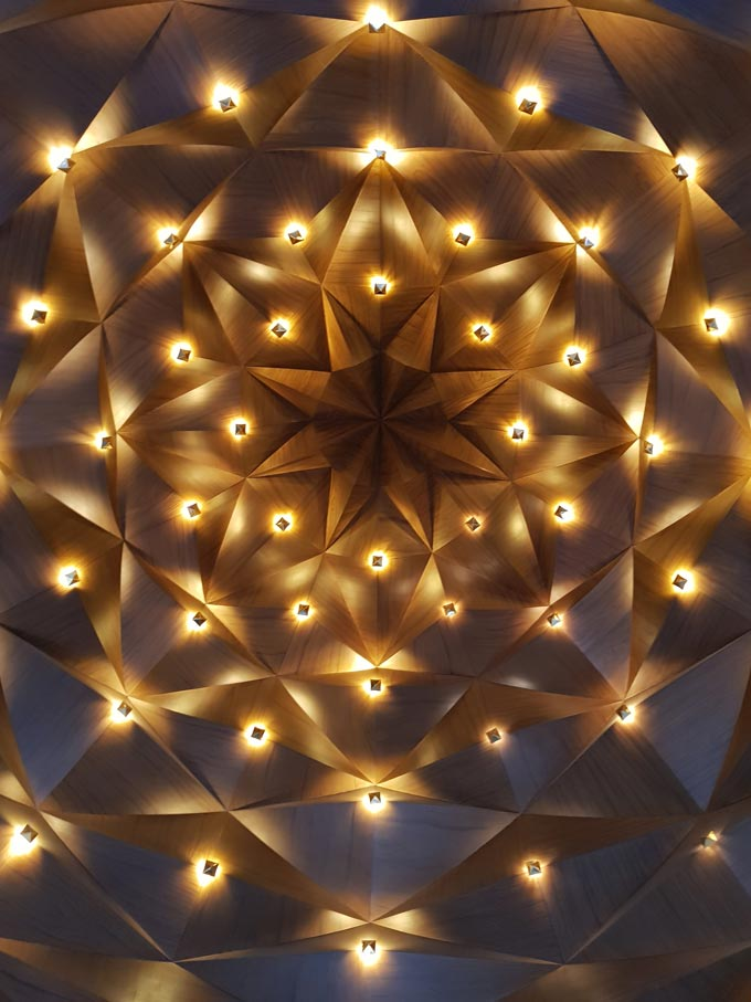 An accent ceiling made of various shaped patterns with lights in between.