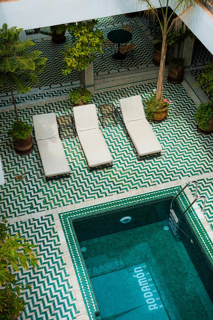 A swimming pool with three sunbeds on one end and a chevron pattern tiled flooring.
