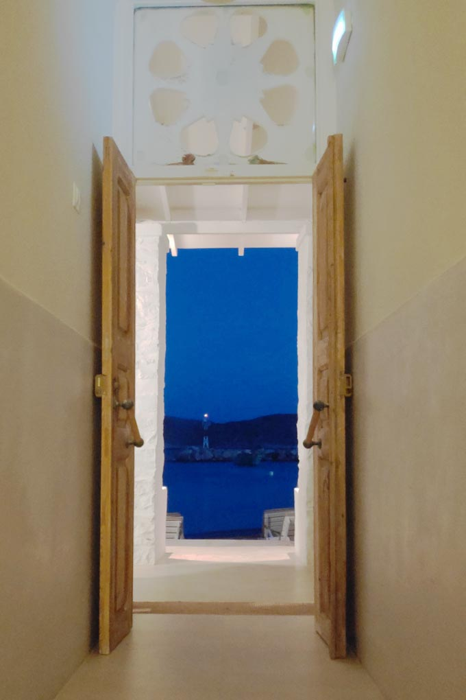 Cycladic minimal style: View from the corridor at the reception area and through the wide open main door, looking out to the beacon across the dock in the background.