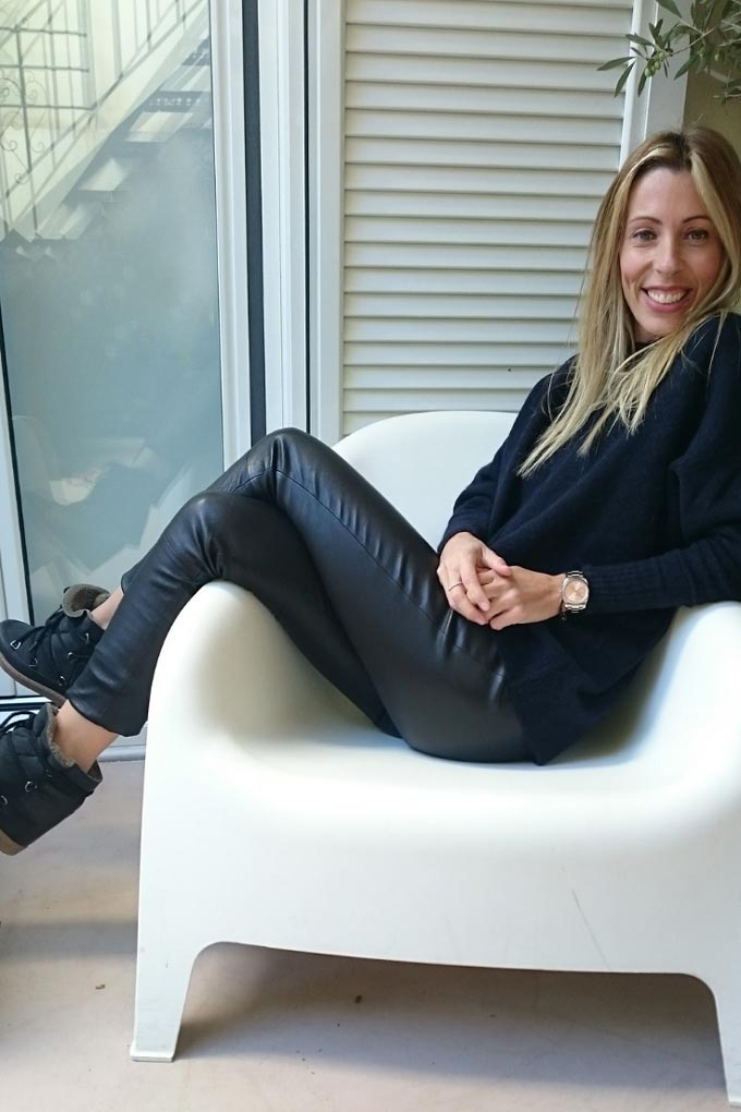 Elisabeth sitting on a white Ikea armchair wearing a pair of real leather pants.
