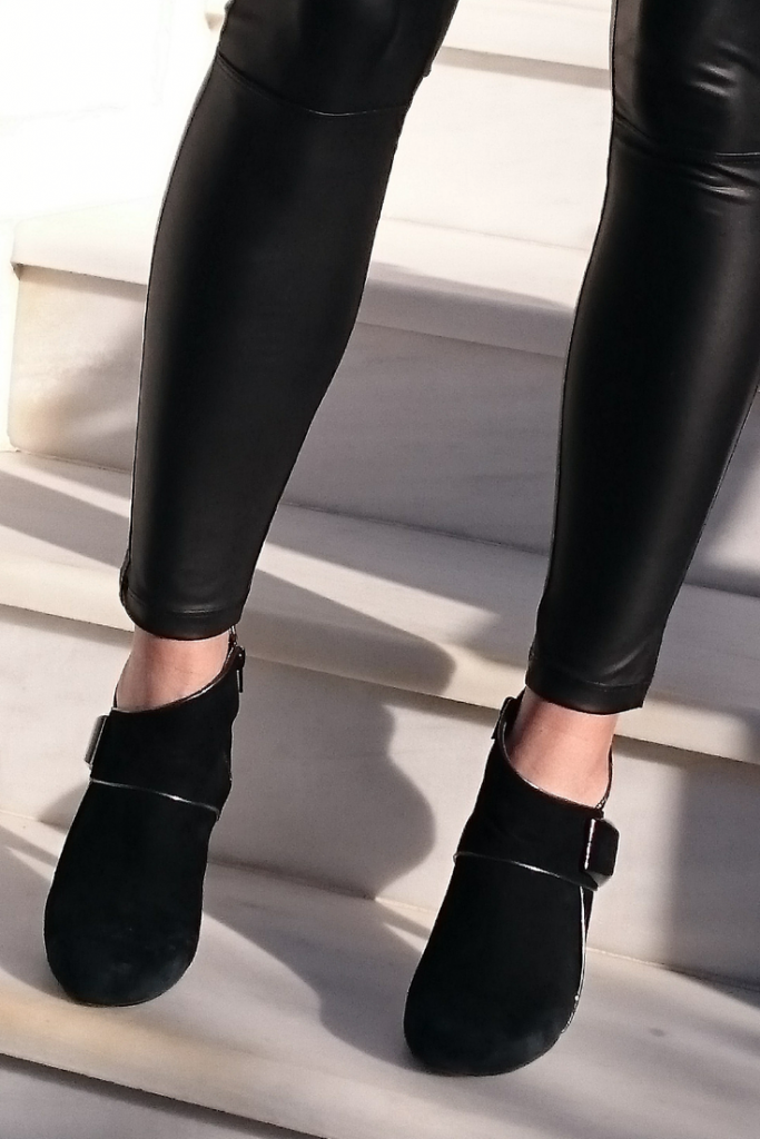 Black faux leather leggings paired with black ankle boots.