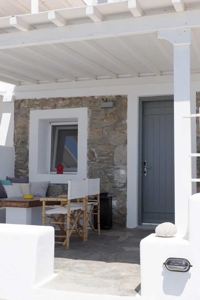 Looking at the exterior of a Cycladic minimal facade and terrace at Bellou Suites in Mykonos.
