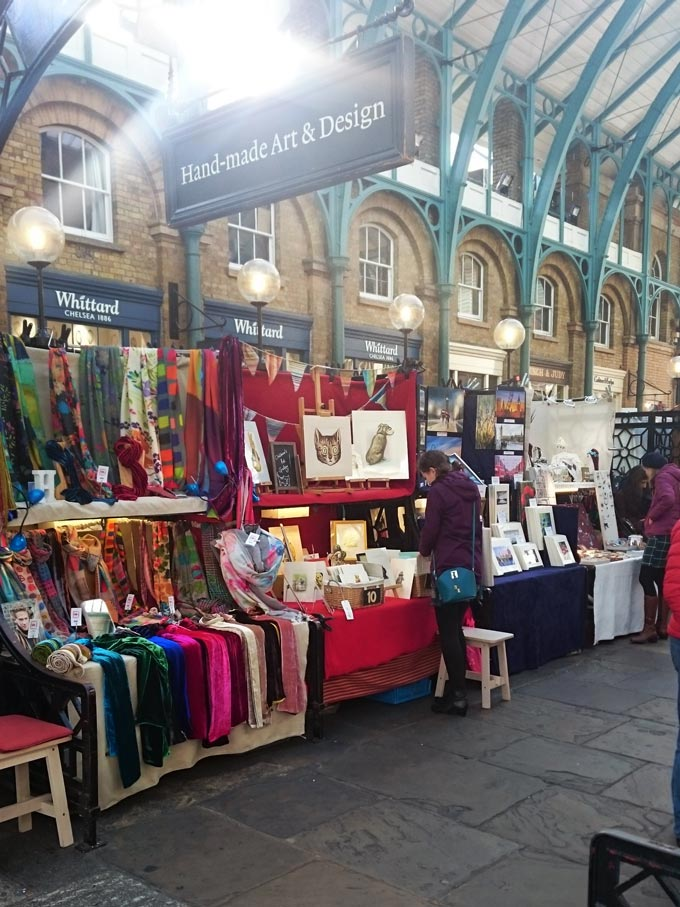 Booths with products for sale from artists and artisans in Covent Garden.